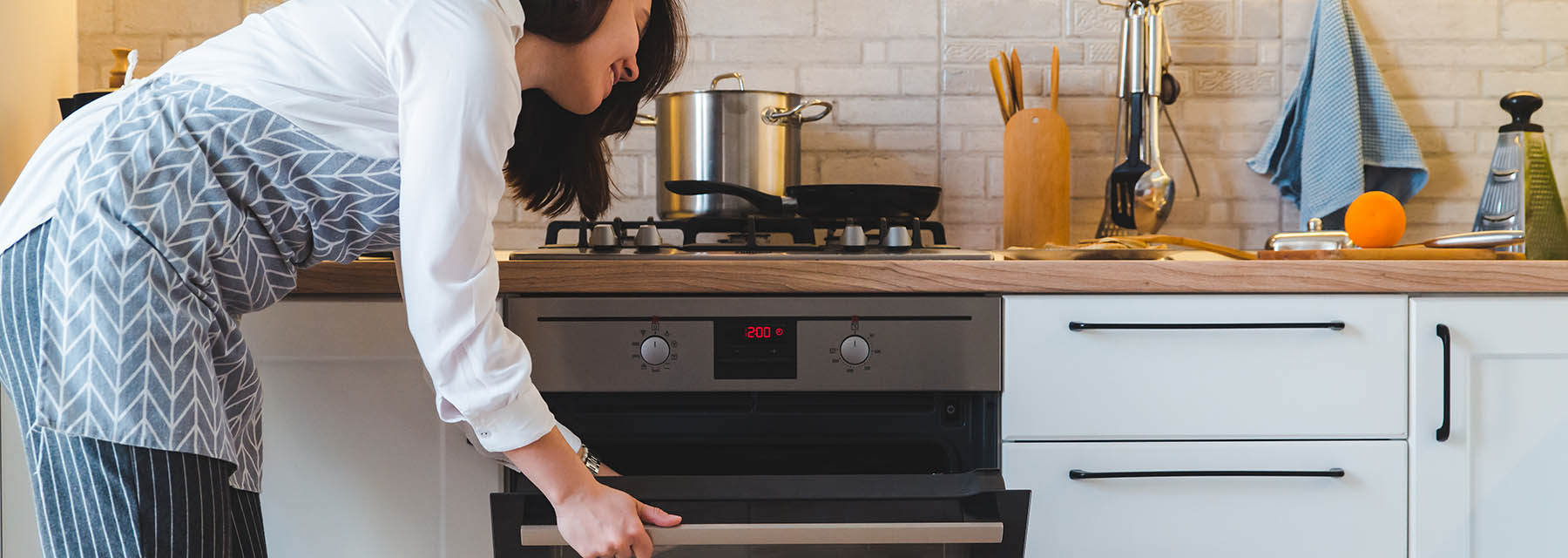 woman opening oven door while cooking on natural gas cooktop