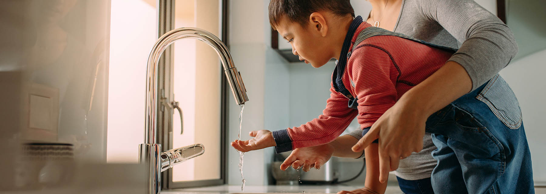 mother helping her son wash his hands under a kitchen faucet