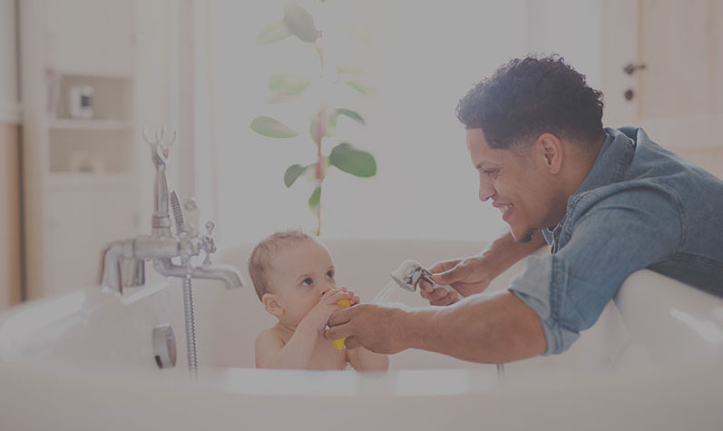 Dad giving his baby a bath in the bathtub